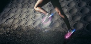 Strong Young woman running, sprinting at night in urban scene